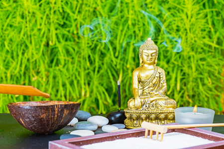 Buddha, incense stick, candle, rake, sand and zen stones as zen garden background