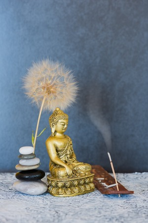 Buddha, pyramid of pebbles, incense stick and dandelion flower as zen background