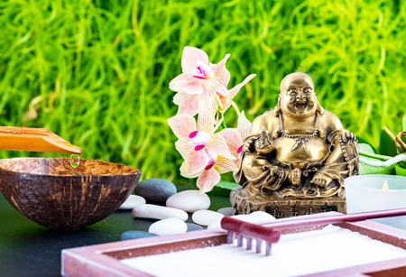Zen garden background with Laughing Buddha or Budai, orchid flower, candle, rake, sand and zen stones Stock Photo