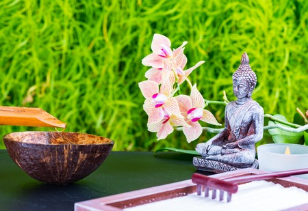 Zen garden background with buddha, orchid flower, candle, rake and zen sand