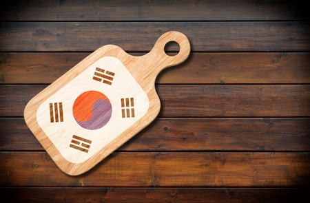 Concept of South Korean cuisine. Cutting board with a South Korea flag on a wooden background Stock Photo