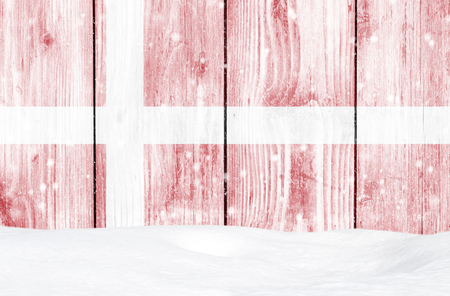Denmark flag as Christmas background with white wooden wall, falling snow and snowdrift Stock Photo