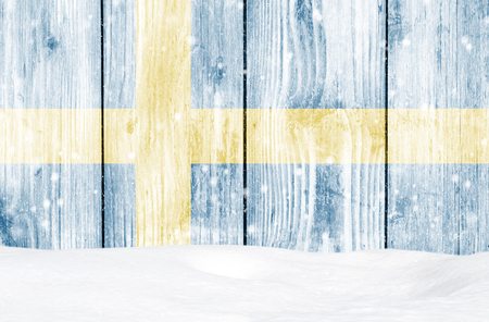 Sweden flag as Christmas background with white wooden wall, falling snow and snowdrift Stock Photo