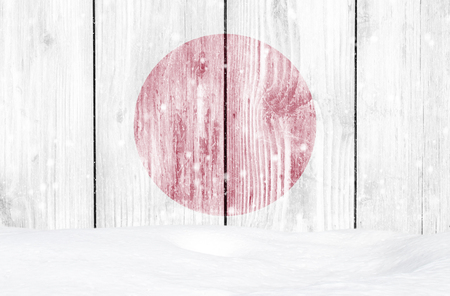 Japan flag as Christmas background with white wooden wall, falling snow and snowdrift Stock Photo
