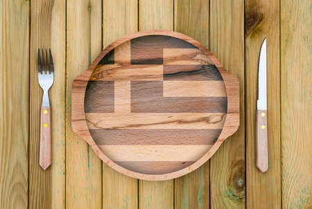 Concept of Greek cuisine. Wooden plate with a Greece flag, fork and knife on a wooden background