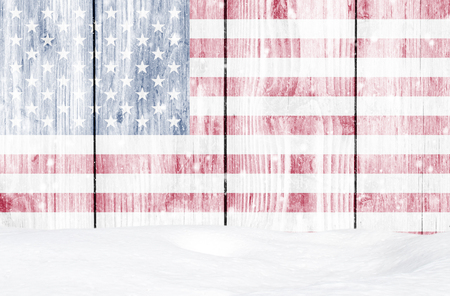 American flag as Christmas background with white wooden wall, falling snow and snowdrift Stock Photo