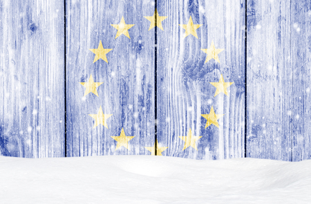 European union flag as Christmas background with white wooden wall, falling snow and snowdrift