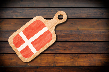 Concept of Danish cuisine. Cutting board with a Denmark flag on a wooden background Stock Photo