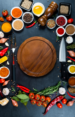 Big set of spices, vegetables,chefs knife, fork for meat and empty wooden round cutting board on a black background