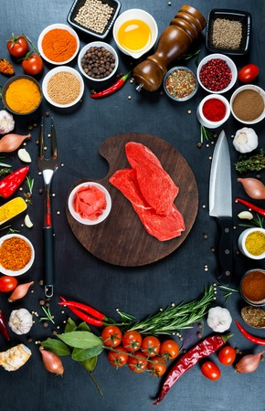Raw beef meat on a wooden round cutting board, kitchen knife, fork for meat, various spices and vegetables on a black background Stock Photo