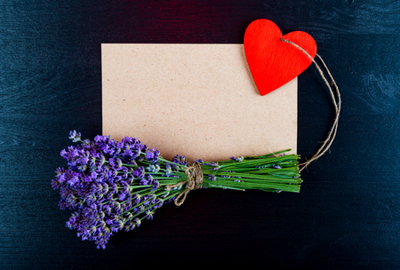 Lavender flowers, blank sheet of paper and heart on a black wooden background