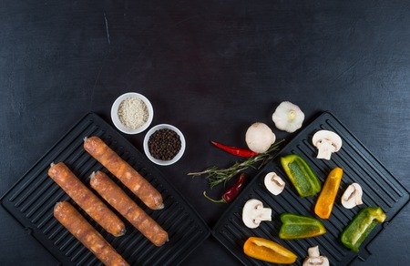 Grilled sausages, spices and vegetables for frying on black background