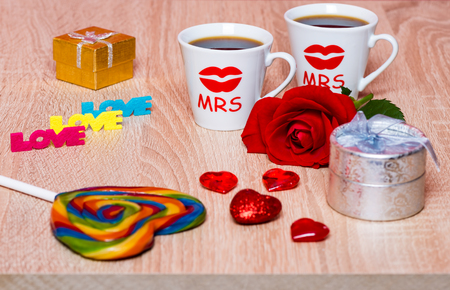 Lesbian marriage concept. Two cups of coffee, rose flower, gift and rainbow lollipop Stock Photo