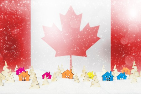 Christmas background with Canadian flag, small wooden houses, Christmas trees and snow. Stock Photo