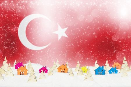 Christmas background with Turkish flag, small wooden houses, Christmas trees and snow. Stock Photo