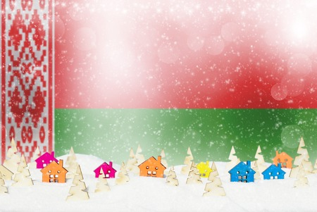 Christmas background with Belarusian flag, small wooden houses, Christmas trees and snow.