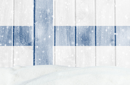 Christmas winter background with wooden wall, falling snow, snowdrift and Finnish flag