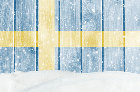 Christmas winter background with wooden wall, falling snow, snowdrift and Swedish flag Banco de Imagens