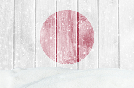 Christmas winter background with wooden wall, falling snow, snowdrift and Japanese flag Stock Photo