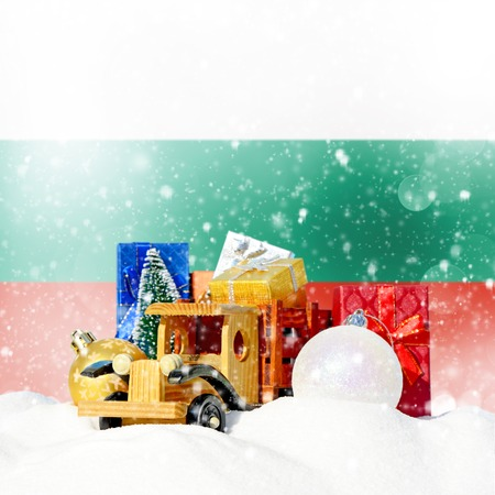 Christmas background.Toy truck with gifts, New Year fir, balls in the snowdrift and Bulgarian flag Stock Photo
