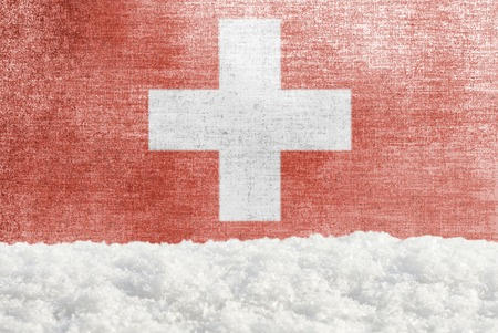 Winter grunge background with snowdrift and Swiss flag in the backdrop
