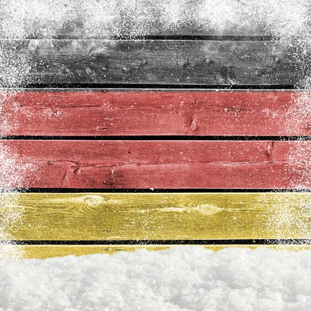 Winter background with wooden wall, falling snow, snowdrift and German flag