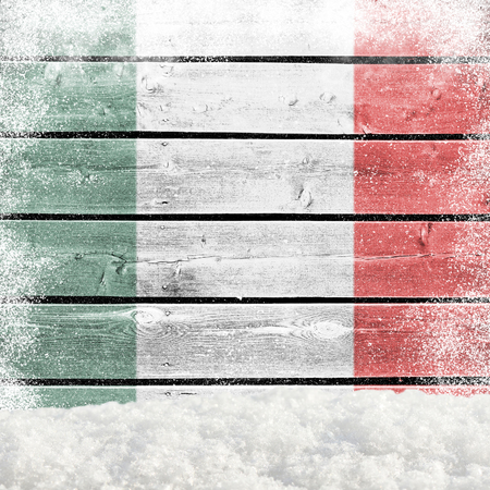 Winter background with wooden wall, falling snow, snowdrift and Italian flag