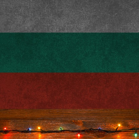 Festive grunge background with Christmas lights on a wooden surface and Bulgarian flag