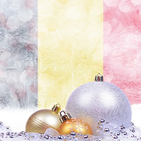 Christmas background with Belgian flag on frosted windowpane, big silver ball and golden balls Imagens