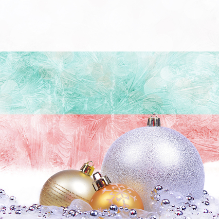 Christmas background with Bulgarian flag on frosted windowpane, big silver ball and golden balls