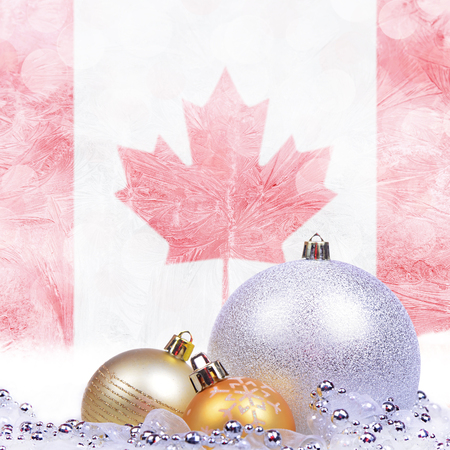 Christmas background with Canadian flag on frosted windowpane, big silver ball and golden balls