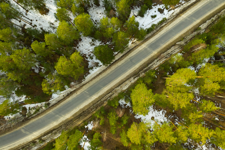 Old asphalt road in the spring forest top drones view Snow melts on the side of the road and between the trees.