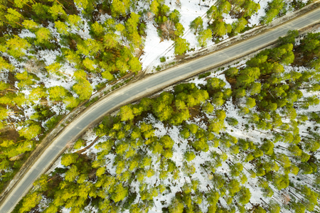 Old asphalt road in the spring forest top drones view. Snow melts on the side of the road and between the trees