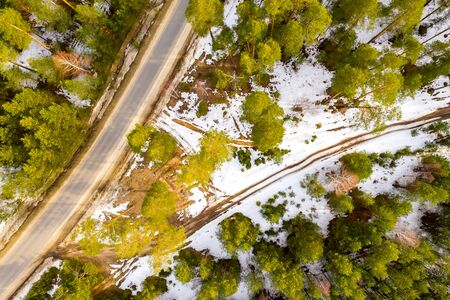 Road in the spring forest. Snow melts on the side of the road and between the trees. Aerial drone shot