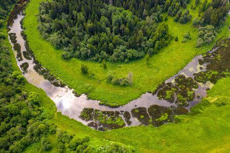 Aerial drone view of river overgrown with reeds and grass cutting trough forest Standard-Bild - 128843385