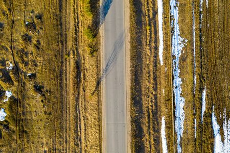 Road in the spring forest. Snow melts on the side of the road and between the trees. Aerial drone shot Standard-Bild - 128843408