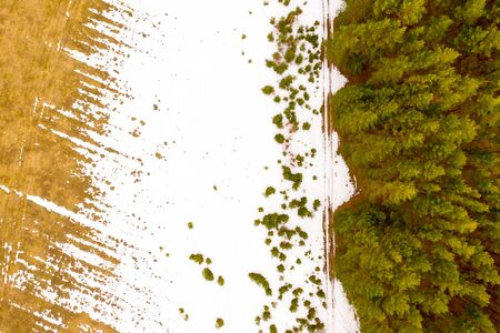 White snow melts on a green agricultural field. Aerial drone view