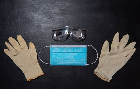 Black medical background with safety goggles, medical mask and two gloves