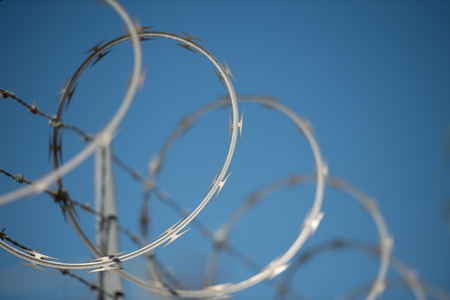 opposites: concertinas razor and barbed wire fence against a blue sky Stock Photo