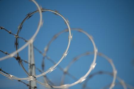 concertinas scheermes en prikkeldraad hek tegen een blauwe hemel