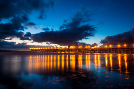 oceanside: pier with lights reflecting on water at sunset in Oceanside,California Stock Photo