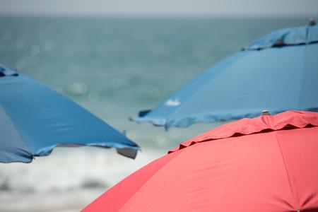 海の背景に赤と青のビーチ パラソル
