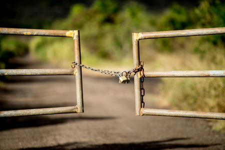 trespass: padlock and chain attached to a metal ranch gate with dirt road in background