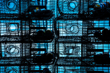 traps: lobster traps stacked silhouetted against blue water