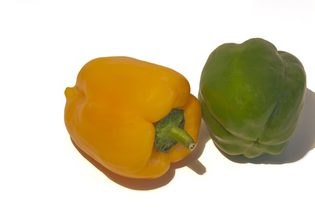 Green and yellow sweet peppers on a white background.