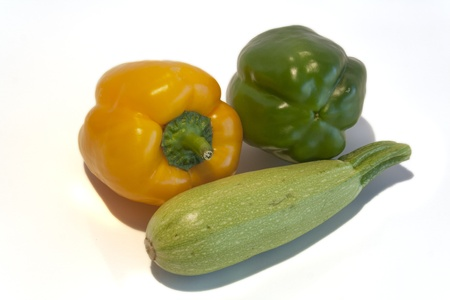 Green and yellow sweet peppers and squash on a white background. Stock Photo