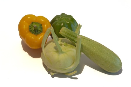 Green and yellow sweet peppers, squash and kohlrabi on a white background.
