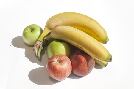 Bananas red and green apples on a white background. Stock Photo