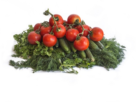 Tomatoes, cucumbers, dill leaves and parsley on the white background. Stock Photo