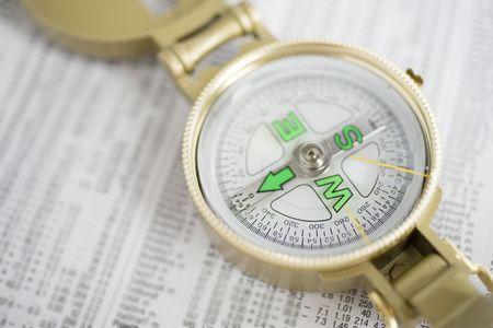 dinero falso: Br�jula dorada en la parte superior de la secci�n financiera del peri�dico